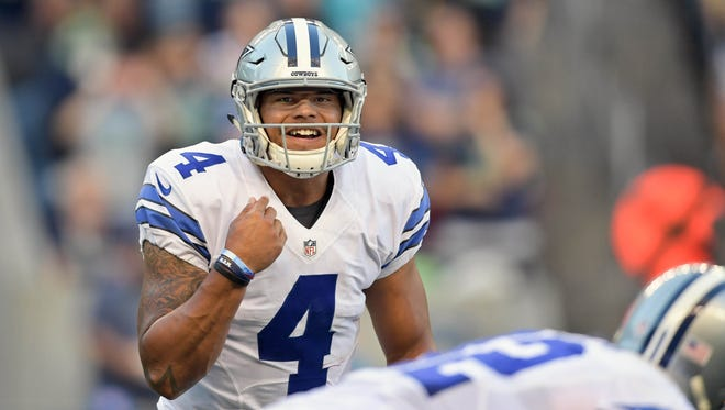 Dallas Cowboys quarterback Dak Prescott (4) makes the call form the line against the Seattle Seahawks during the first half of an NFL football game at CenturyLink Field.
