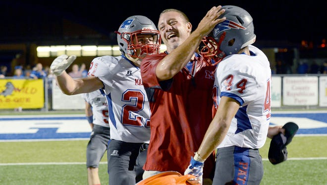 Madison football coach Ben Rhodarmer celebrates with his players after Friday's 47-44 win at Brevard.