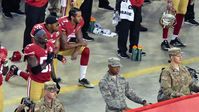 San Francisco 49ers quarterback Colin Kaepernick (7) and teammate Eric Reid (35) kneel during the national anthem before an NFL game against the Los Angeles Rams.