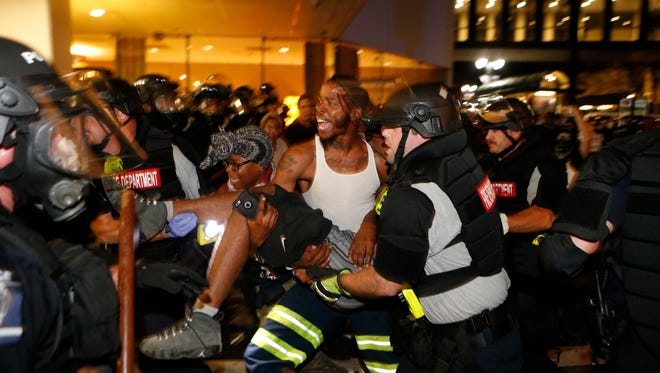 Police and protesters carry a seriously wounded protester into the parking area of the the Omni Hotel during a march to protest the death of Keith Scott September 21, 2016 in Carolina. Scott, who was black, was shot and killed at an apartment complex near UNC Charlotte by police officers, who say they warned Scott to drop a gun he was allegedly holding.  (Photo by Brian Blanco/Getty Images) ORG XMIT: 671694357 ORIG FILE ID: 609606986