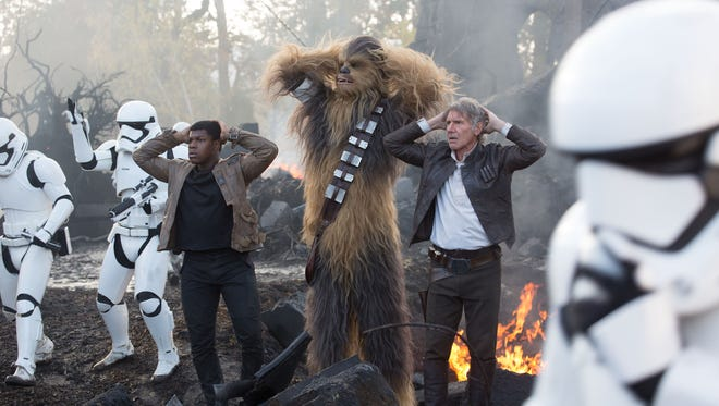 """Finn (John Boyega), Chewbacca (Peter Mayhew), Han Solo (Harrison Ford) and company helped propel """"Star Wars: The Force Awakens"""" to new box office heights."""