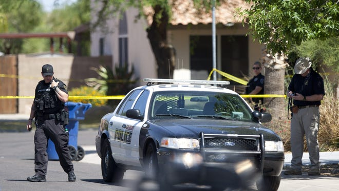 Police respond to a shooting rampage at a Gilbert home May 2, 2012. The shooting, which left four adults and an infant dead, was one of the crimes that led to the creation of the town's family-violence unit.