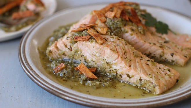 FILE -This Nov. 9, 2015, photo, shows salmon poached in green salsa and topped with baked chips in Concord, N.H. This dish is from a recipe by Sara Moulton.
