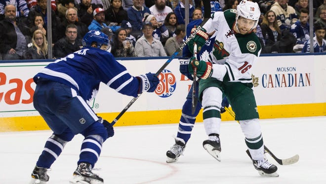 Minnesota Wild left wing Jason Zucker, right, battles for the puck with Toronto Maple Leafs defenseman Connor Carrick during the third period of an NHL hockey game in Toronto on Wednesday, Dec. 7, 2016. (Chris Young/The Canadian Press via AP)