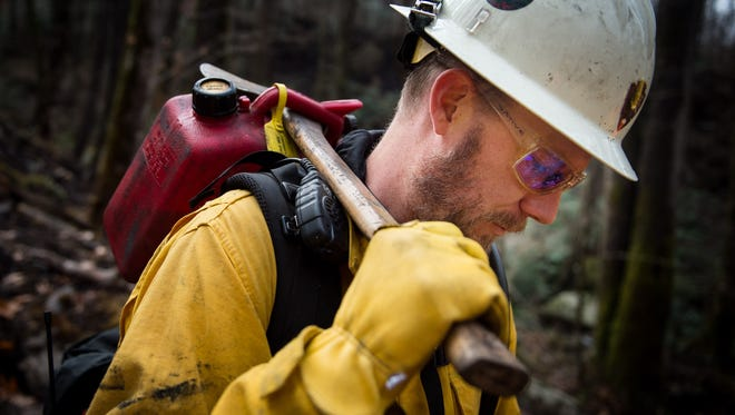 National Park Service firefighter Dave Frey, from the Rocky Mountain National Park in Colorado, carries equipment up the Rainbow Falls Trail in the Great Smoky Mountains National Park near Gatlinburg, Tenn., Wednesday, Dec. 7, 2016. Hundreds of firefighters continue to conduct operations within the park as the Chimney Top 2 Fire is reported to be 64% contained as of Wednesday morning.
