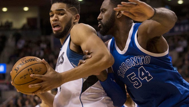 Minnesota Timberwolves centre Karl-Anthony Towns, left, is guarded by Toronto Raptors forward Patrick Patterson during the second half of an NBA basketball game in Toronto on Thursday, Dec. 8, 2016. (Chris Young/The Canadian Press via AP)