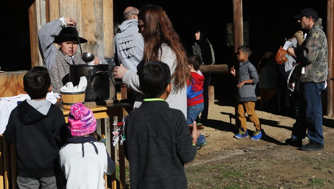 Christopher Watson, 11, of Orland serves wassail, a type of hot cider, to people participating Saturday at the William B. Ide Adobe State Historic Park's 39th annual Pioneer Christmas Party in Red Bluff.