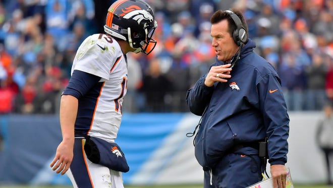 Denver Broncos head coach Gary Kubiak (R) talks with Broncos quarterback Trevor Siemian (13) during a game against Tennessee on Dec. 11.
