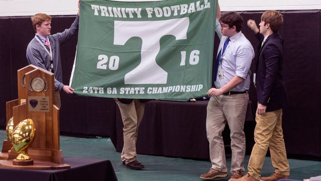 Trinity students unveil the newest addition to their state title flag collection during a celebration ceremony on Tuesday morning. 1/10/17