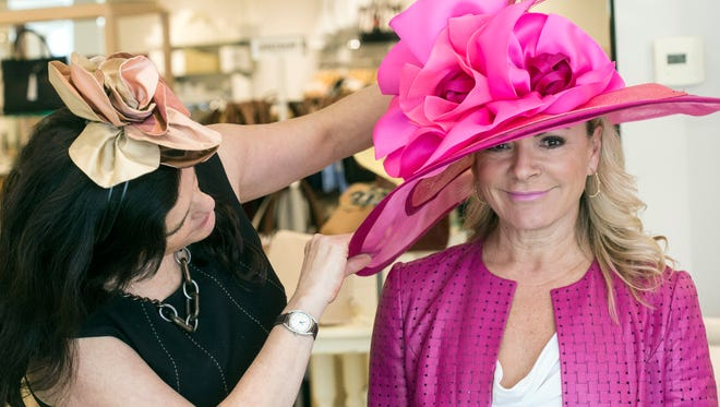 Rhonda Jo Conner tries on one of the colorful creations of milliner Christine Moore available at Rodes for Her. 3/9/17