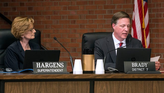 JCPS Superintendent Donna Hargens listens as Board of Education member Chris Brady reads the announcement that Hargens will step down from her post effective July 1, 2017. April 13, 2017
