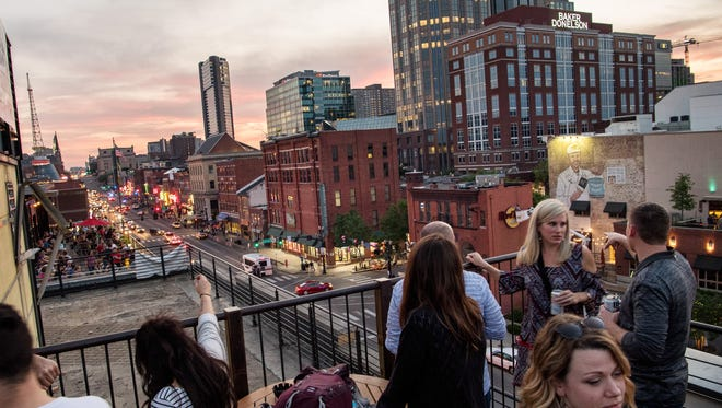 Guests enjoy the view at the Acme Feed and Seed rooftop bar in Nashville.