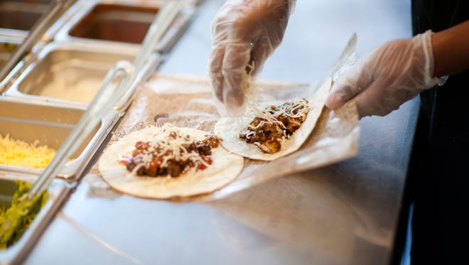 An employee constructs tacos at a Chipotle location.