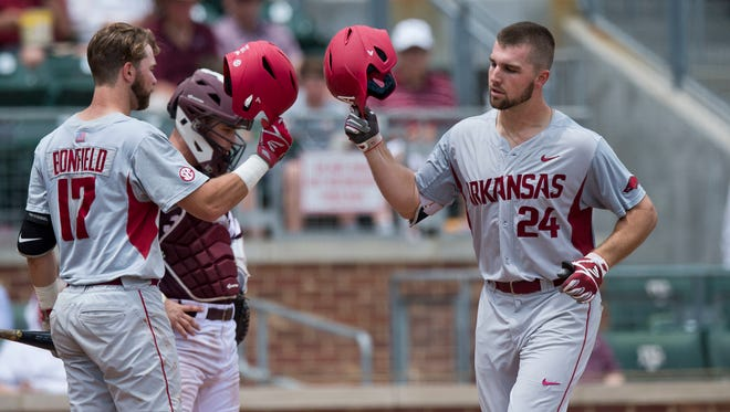 Arkansas first baseman Chad Spanberger (24) taps helmets with teammate Luke Bonfield (17) after rounding the bases on a home run during a college baseball game, Saturday, May 20, 2017, at Olsen Field in College Station, Texas. (Timothy Hurst/College Station Eagle via AP)