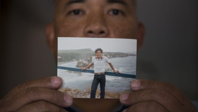 Francis Charfauros holds a photo of himself, June 14, 2017, that was taken in the summer of 1983.
