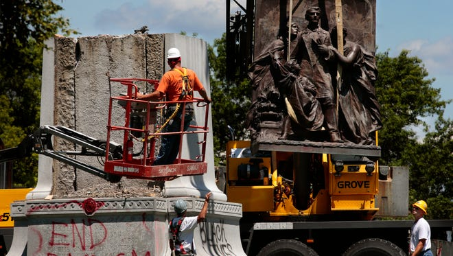 A crane removes a sculpture from a Confederate monument in Forest Park on Monday, June 26, 2017, in St. Louis. Crews on Monday began dismantling the divisive monument after the city and the Missouri Civil War Museum reached an agreement to have it moved. (Robert Cohen /St. Louis Post-Dispatch via AP)