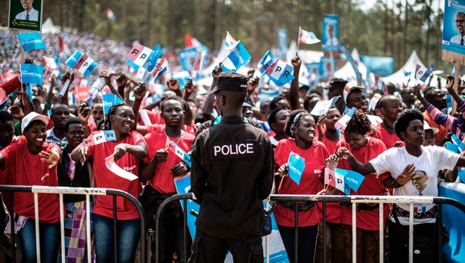 A Rwandan police officer stands guard as supporters of President Paul Kagame gather for a rally in Gakenke, on July 31, 2017, ahead of Friday's presidential election.