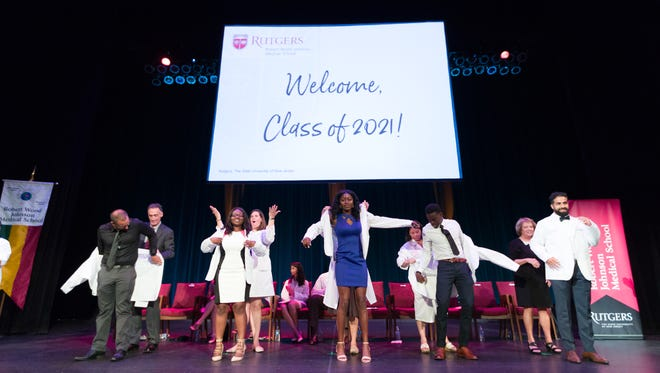 First-year medical students are coated by faculty members of Rutgers Robert Wood Johnson Medical School during the school's White Coat Ceremony at the State Theatre in New Brunswick.