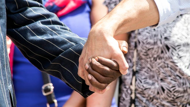 Hands were held in group prayer during a peaceful counter-protest in Jefferson Square related to this weekend's violence in Virginia. 8/13/17
