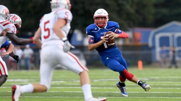 West Henderson quarterback Dalton Cole looks for an opportunity to pass against the Hendersonville defense  during their game at West Henderson High School on Friday, Aug. 25, 2017. The Bearcats defeated the Falcons 29-28.