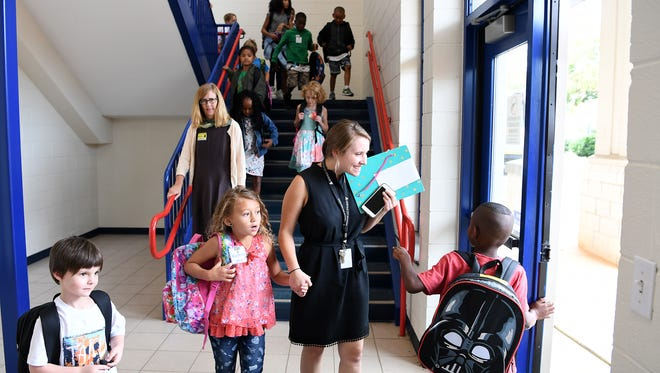 Claxton Elementary School teacher second grade teacher Becca Wertheim helps students to their buses at the end of the first day of school on Monday, Aug. 28, 2017.