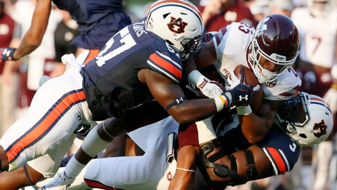 Mississippi State Bulldogs receiver Keith Mixon (23) is tackled by Auburn Tigers linebacker Deshaun Davis (57) and lineman Marlin Davidson (3).