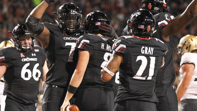 UC Bearcats celebrate with Hayden Moore after scoring UC's first touchdown during the UC vs. UCF Knights game at Nippert Stadium on Saturday Oct. 7, 2017.