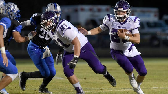 Mitchell quarterback Ben Young makes his way through the Polk County defense as he runs the ball during their game at Polk County High School on Thursday, Oct. 19, 2017. The Mountaineers defeated the Wolverines 25-7.