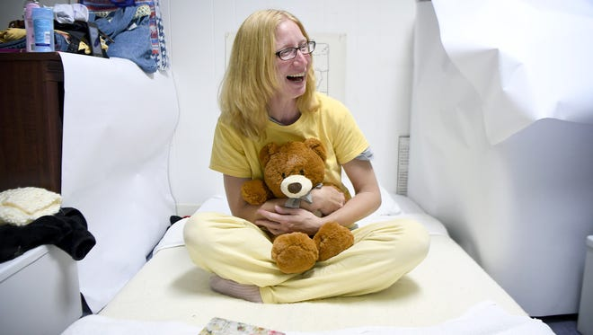 """Pam Pressley laughs as she hugs a teddy bear jokingly named """"Ray, Ray"""" after her boyfriend as she sits on her bed in the basement of Grace Episcopal Church where she and about 10 other women were spending a week of nights with the Room in the Inn program on Thursday, Nov. 16, 2017. Pressley's boyfriend is currently finding shelter at the Salvation Army while she stays with the women-only program."""
