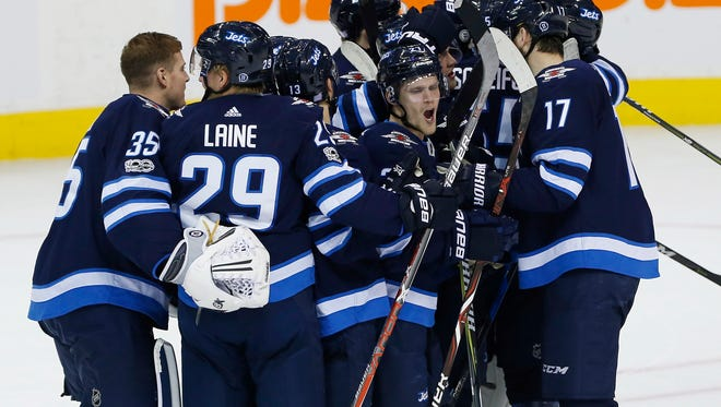 Winnipeg Jets' Nikolaj Ehlers, centre, and teammates celebrate after defeating the Philadelphia Flyers in a shootout in NHL hockey game action in Winnipeg, Manitoba, Thursday, Nov. 16, 2017.