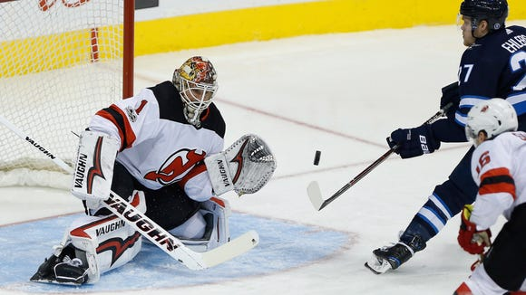 New Jersey Devils goaltender Keith Kinkaid (1) saves a shot by Winnipeg Jets' Nikolaj Ehlers (27) during the third period of an NHL hockey game in Winnipeg, Manitoba, Saturday, Nov. 18, 2017. The Jets defeated the Devils 5-2. (John Woods/The Canadian Press via AP)