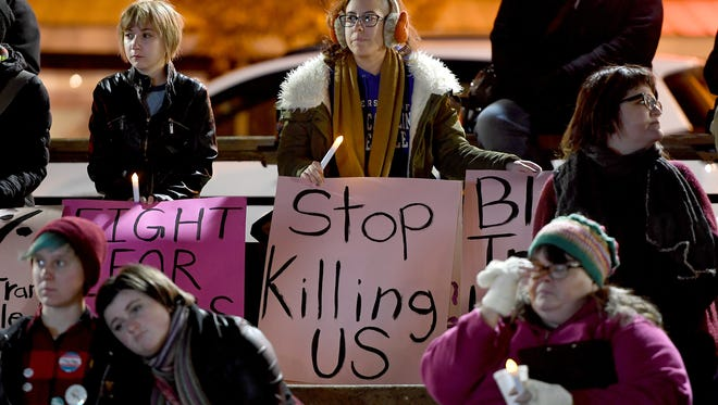 """Sam Jones holds a sign that reads """"Stop Killing Us"""" as the names of 320 people who died as the result of anti-transgender violence in the last year during a Transgender Day of Remembrance ceremony in Prichard Park on Monday, Nov. 20, 2017. The 320 names included 27 people who were killed in the United States since the last day of remembrance."""