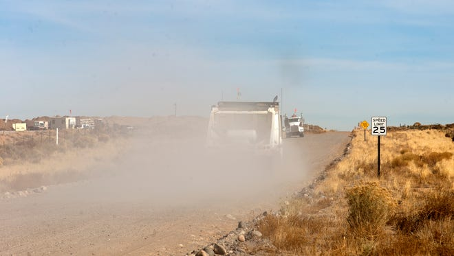 Trucks haul dirt at the Evirotech land farm Monday south of Bloomfield.