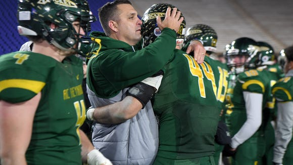 Reynolds head coach Shane Laws comforts senior Frank Torres after the Rockets' 27-17 loss to New Hanover in the NCHSAA 3AA football state championship game at Wallace Wade Stadium at Duke University in Durham on Saturday, Dec. 9, 2017.