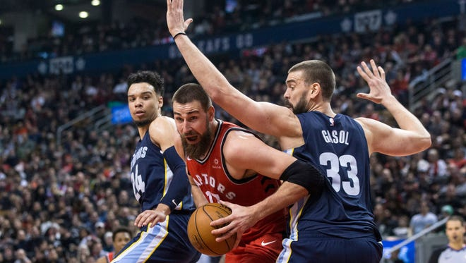 Toronto Raptors center Jonas Valanciunas (17) looks to lay off a pass despite pressure from Memphis Grizzlies center Marc Gasol (33) and forward Dillon Brooks (24) during first-half NBA basketball game action in Toronto, Sunday, Feb. 4, 2018. (Chris Young/The Canadian Press via AP)