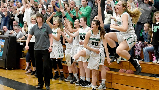Mountain Heritage's Olivia Grindstaff leaps into the air as she and the rest of the Cougar bench celebrate their 61-44 win over Wilkes Central in the fourth round of the NCHSAA 2A playoffs at Mountain Heritage High School on Tuesday, Feb. 27, 2018.