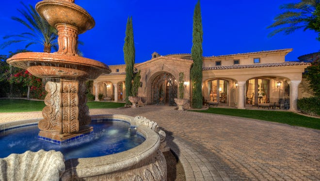 The home is an ornate European-style estate, with a circular stone driveway flanked by palm trees and an entry fountain.