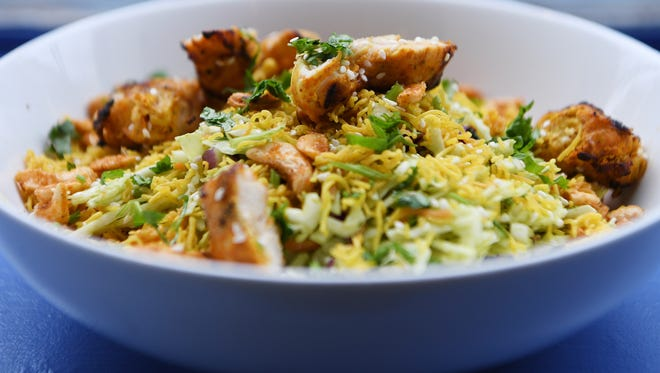The Desi Salad, shown here topped with chicken tikka, is filled with shredded white and red cabbage, carrots, scallions and roasted cashews, cilantro and a cumin-lime vinaigrette.