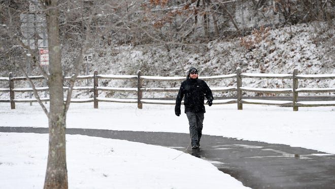 A man walks through Carrier Park in the snow on Wednesday, March 14, 2018.
