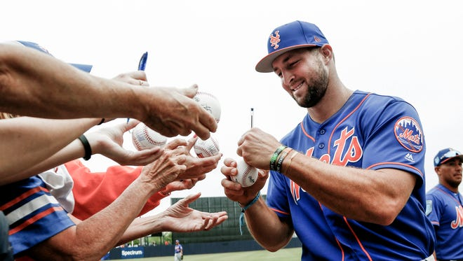 New York Mets outfielder Tim Tebow (signs autographs before a game against the New York Yankees at George M. Steinbrenner Field in Tampa Fla., on March 10.
