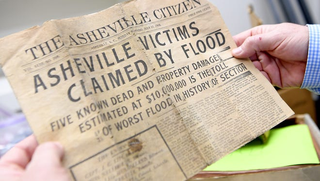 Reporter John Boyle holds a newspaper from 1916 found in the Asheville Citizen Times building at 14 O Henry Avenue downtown.