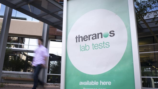 A Theranos sign is seen on Sept. 26, 2016, at SkySong in Scottsdale. Theranos has laid off most of its remaining workforce as it seeks to preserve cash and delay a bankruptcy filing for a few months, the Wall Street Journal reported Tuesday.