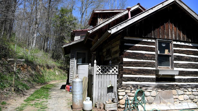 Clark and Mary Floyd moved to their home in Leicester in 1994. The side view is the exterior of the kitchen, which was added to the original structure, built in 1888, in 1979. The original cabin was made of poplar and the stones at the base are river stones.