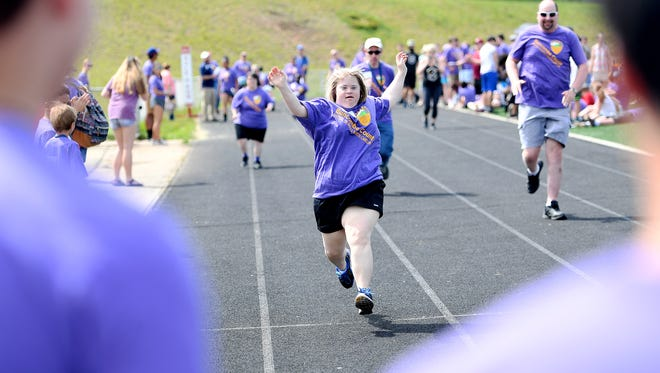 Sue Eversman, an independent competitor, raises her arms in celebration as she nears the finish line in the 50-meter run during the Buncombe County Special Olympics Spring Games at Roberson High School on Thursday, May 3, 2018.