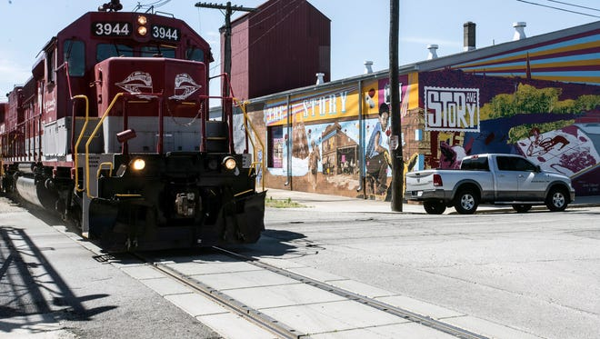 A train runs across Story Avenue in Butchertown in an area mixed with art murals and industry. 5/24/18
