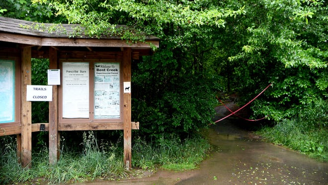 A sign and some red tape turn hikers and bikers away at a trailhead in the Bent Creek Experimental Forest on Tuesday, May 29, 2018. All of the trails in the Bent Creek Experimental Forest were closed by the U.S. Forest Service until at least Friday, June 1 due to prolonged heavy rains.