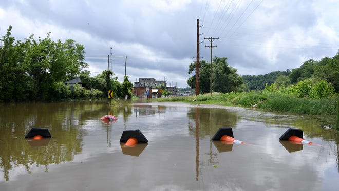 The French Broad River floods into Lyman Street in the River Arts District on Wednesday, May 30, 2018.