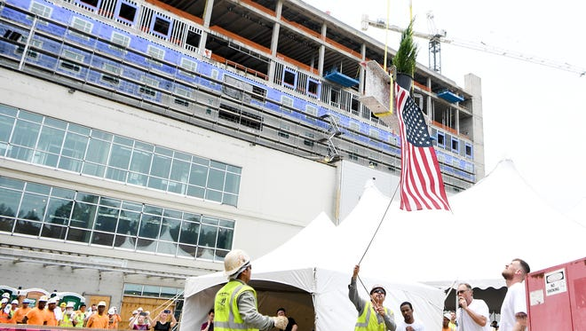 One of the two final beams is hoisted to the top of the Mission Hospital for Advanced Medicine in a topping off ceremony on Thursday, June 28, 2018. The beam had the traditional symbolic pine tree and American flag attached to it as it was secured at the top of the building. Construction began on the new hospital building two years ago and Mission expects to occupy the space by Fall 2018.