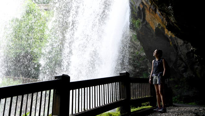 Citizen Times outdoors reporter Karen Chávez.  takes in the cool spray behind Dry Falls near Highlands on July 25, 2018.
