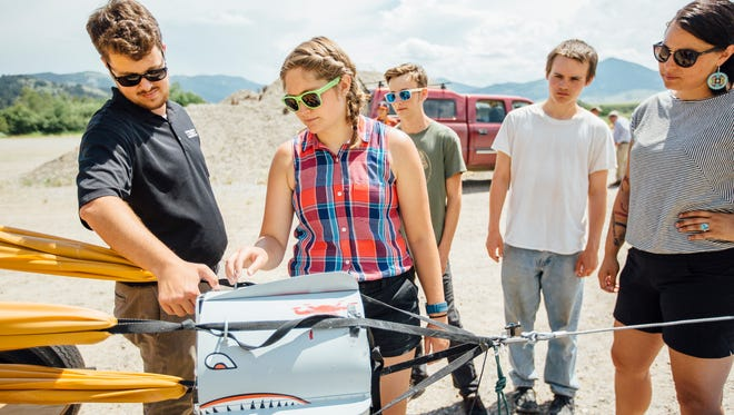 Madison Tandberg, an undergraduate student in mechanical engineering at Montana State University, center, explains the payload bucket of the slingshot used to crash test drones to Mike Reininger from the Federal Aviation Administration, left, Tuesday, July 17, 2018, as MSU undergraduate and graduate students in mechanical and industrial engineering with Professor Doug Cairns, along with students in the Montana Apprenticeship Program, run crash tests of small unmanned aerial vehicles at the MSU Fort Ellis Research Farm, near Bozeman, Mont. The data and observations made from these tests can help determine safety regulations for aircraft.MSU Photo by Adrian Sanchez-Gonzalez